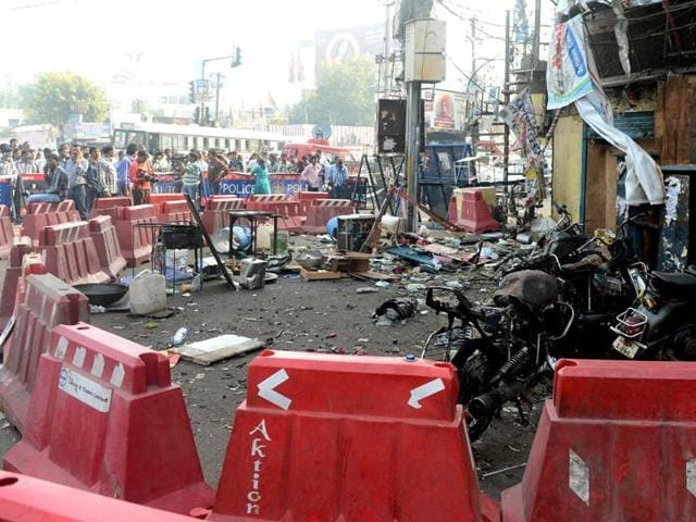 One of the blast sites in Hyderabad is cordoned off as police and pedestrians look on.