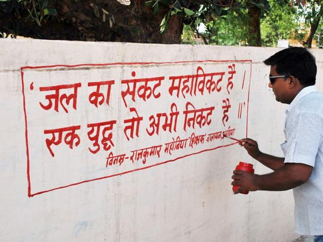 Teacher Rajkumar Mahobia paints a wall of a school in Umaria district.