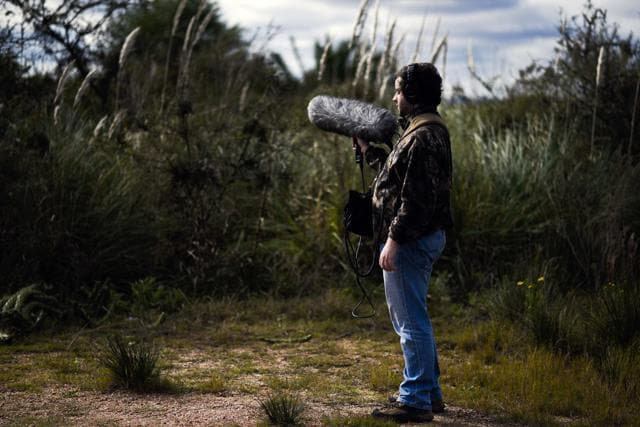 Juan Pablo Culasso stands with his recording equipment in a natural reserve on the outskirts of Montevideo, Uruguay.