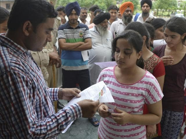 Students getting their admit cards checked at Punjab PMET's Amritsar centre on Saturday.