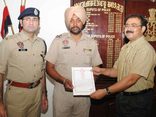 Commisioner of police Arpit Shukla honouring assistant sub-inspector Mohan Singh in Jalandhar on Saturday.(HT Photo)