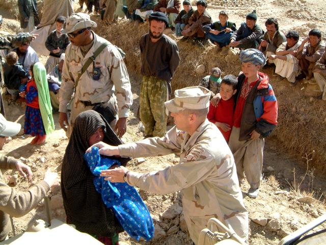 File photo of US civil affairs soldier based with a Provincial Reconstruction team hand out humanitarian relief to local Afghans in Bamiyan province.
