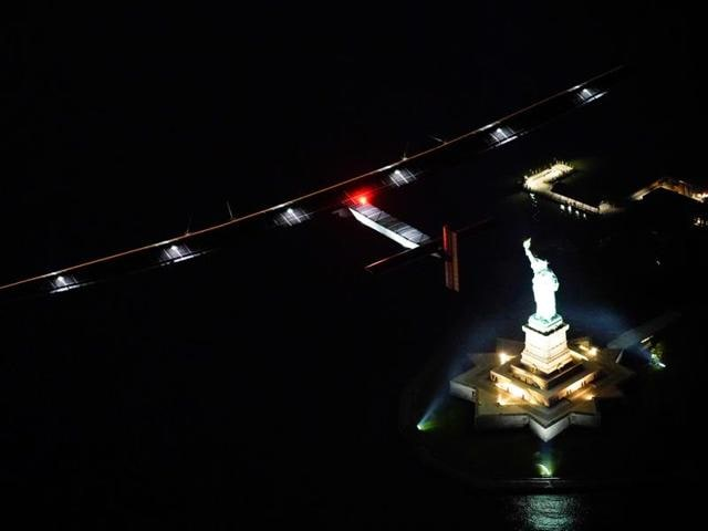 The Solar Impulse 2 flies past the Statue of Liberty, as it approaches New York City for landing at Kennedy