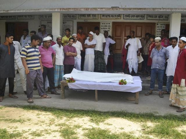 Locals surround the body of a Hindu holy man after assailants hacked him to death in Pabna, Bangladesh, on June 10, 2016.  Hindus in the Muslim-majority country want the Indian government to take up the matter of their safety and security with Dhaka.
