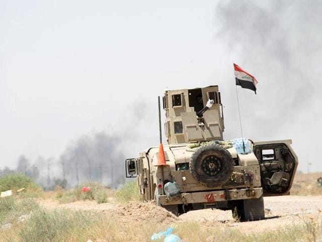 A member of the Iraqi security forces rides in a military vehicle on the outskirts of Falluja, Iraq, June 11, 2016.  Iraqi troops attacked IS positions south of Mosul on Sunday.