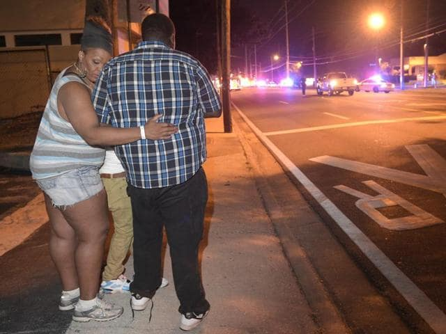 Bystanders wait down the street from a multiple shooting at the Pulse nightclub in Orlando.