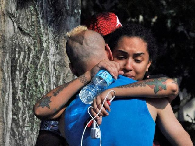 Friends and family members embrace outside the Orlando Police headquarters during the investigation of a shooting at the Pulse nightclub, where people were killed by a gunman, in Orlando, Florida.