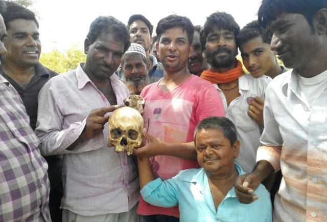 Villagers with the skull found in the forests of Begun village in Chittorgarh district.