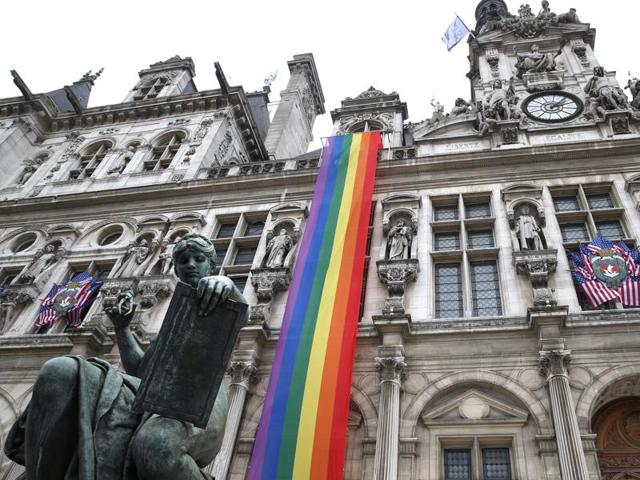 American flags and a rainbow banner hang at the Paris City Hall Monday, June 13, 2016 in Paris.