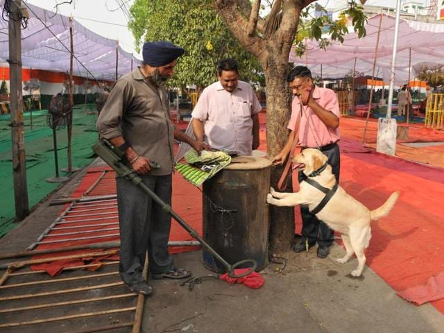 An anti-sabotage team scanning the dharna venue with the help of a sniffer dog in Jalandhar on Sunday; and (right) a hoarding put up by a Congress leader to welcome party leaders to Jalandhar.