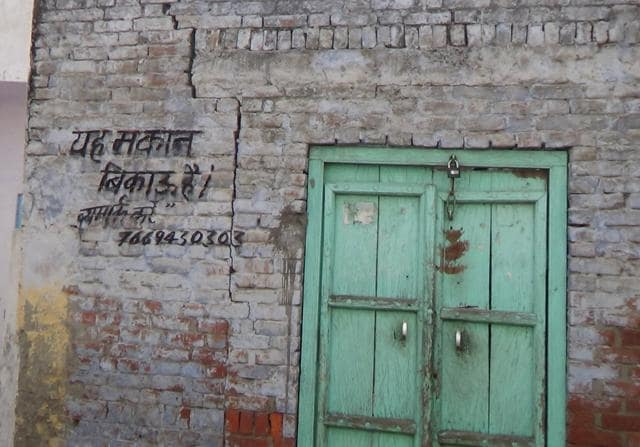 Varun Kumar, with his police security at his shop in main bazar, Kairana. His brother's day light murder in August 2014 by Mukhim Kala brought crime into the limelight in Kairana