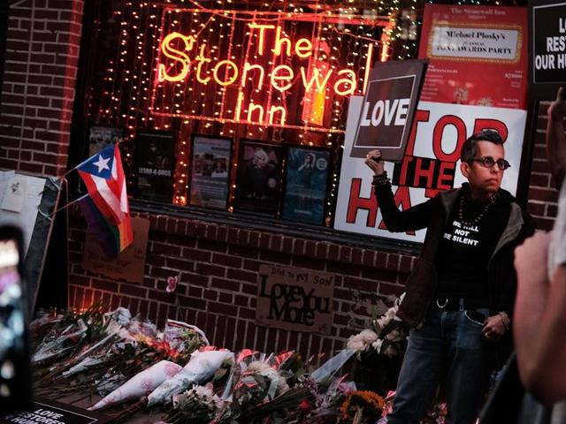 Mourners gather outside the iconic New York City gay and lesbian bar The Stonewall Inn to light candles,lay flowers and grieve for those killed in Orlando on June 12, 2016 in New York City.