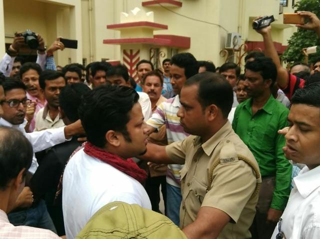 A policeman escorts Trinamool Congress MP Anupam Hazra during a protest demonstration at  Visva Bharati  University campus.
