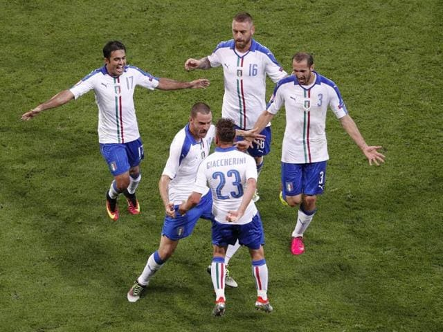 Italy's Emanuele Giaccherini celebrates with his teammates in the dug out after scoring their first goal.