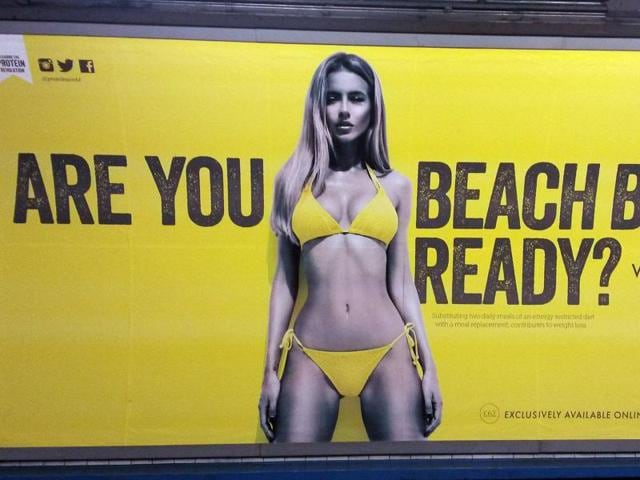 File photo of a Protein World advertisement displayed in an underground station in London. Mayor Sadiq Khan has banned advertising that promotes unhealthy body images on the city's subway network. Starting July, Transport for London will not allow ads that cause pressure to conform to