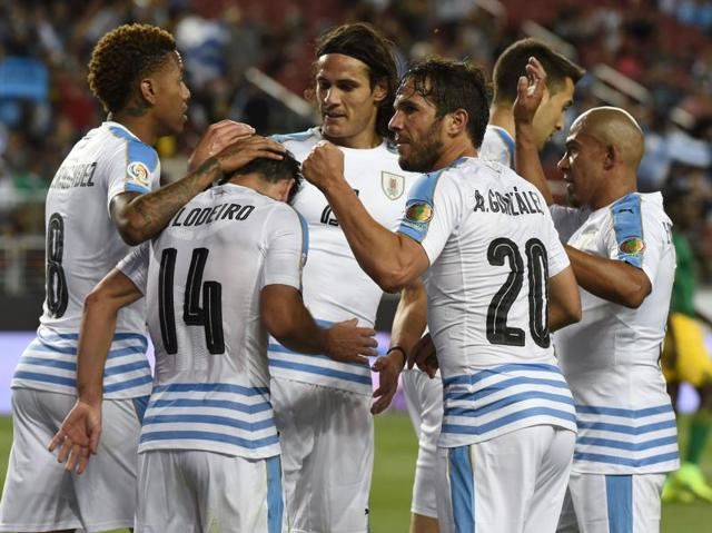 Players of Uruguay celebrate an own-goal by Jamaica's Je-Vaughn Watson during their Copa America match.