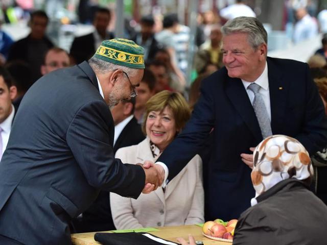 German President Joachim Gauck (right) shakes hands with Imam Abdallah Hajjir at a Ramzan fast break with members of the Muslim community in Berlin on June 13.