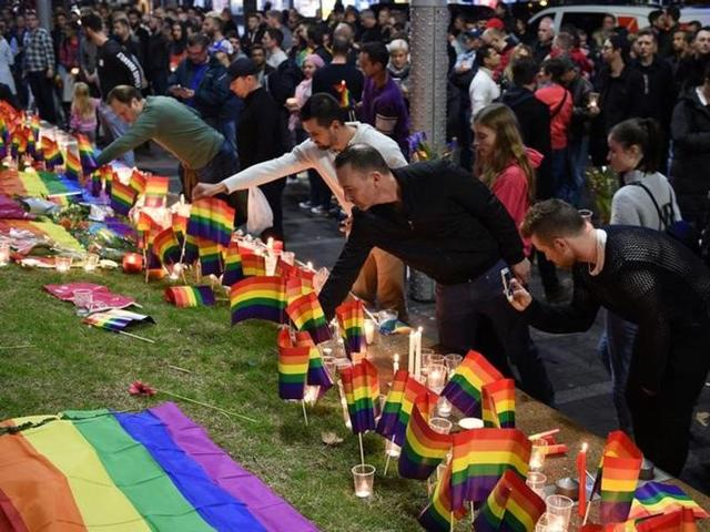 People gather at a vigil in solidarity for the victims of the Orlando nightclub mass shooting at Taylor Square in Sydney.