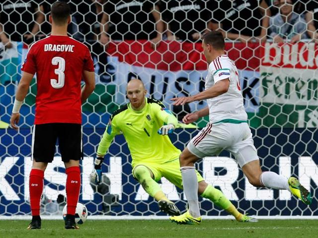 Hungary's Adam Szalai (right) scores the opening goal past Austria goalkeeper Robert Almer during the Euro 2016 Group F football match between Austria and Hungary at the Nouveau Stade in Bordeaux, France.