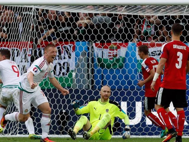 Hungary's Adam Szalai (left) celebrates after scoring the opening goal past Austria goalkeeper Robert Almer, center, during the Euro 2016 Group F  match against  Austria.