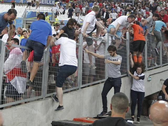 Spectators try to escape from Russian supporters who went on a charge in the stands right after the Euro 2016 Group B football match between England and Russia, at the Velodrome stadium in Marseille, France.