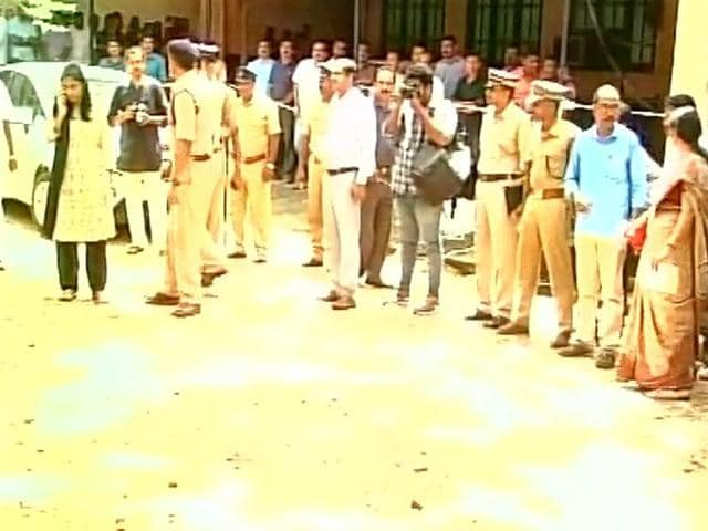 Police officials inspect the site of a bomb blast at a court complex in Kollam.