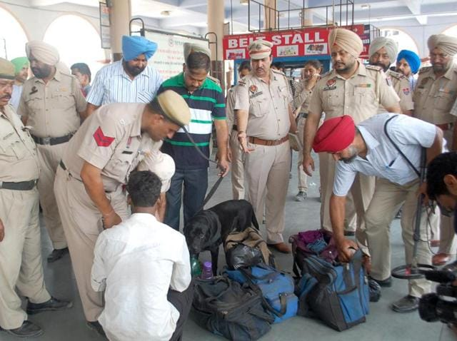 Cops checking the luggage of passengers at the ISBT in Amritsar on Tuesday.