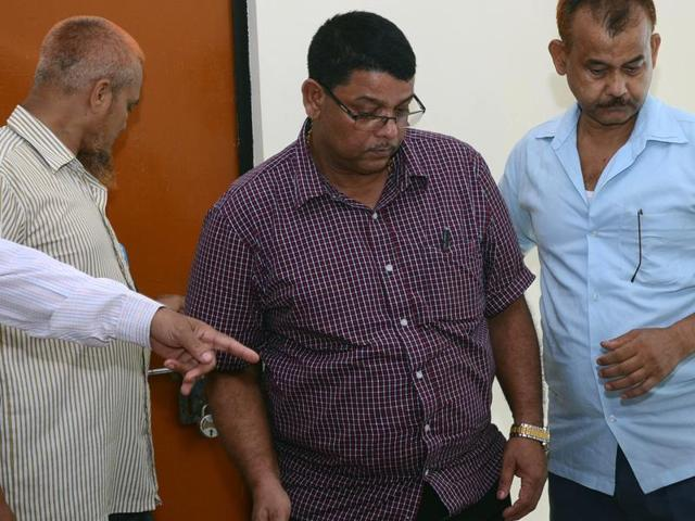 District forest officer Mahat Chandra Talukdar is questioned by media after being arrested by the anti-corruption branch of police in Assam.