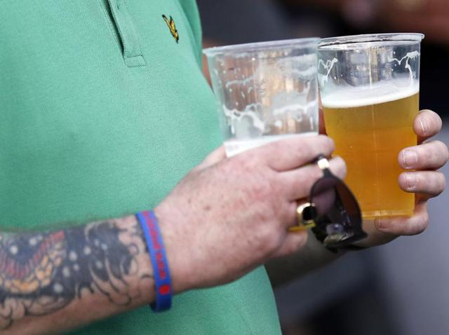 An England supporter carries beer shortly before a drinking ban comes into effect in Lille, France.