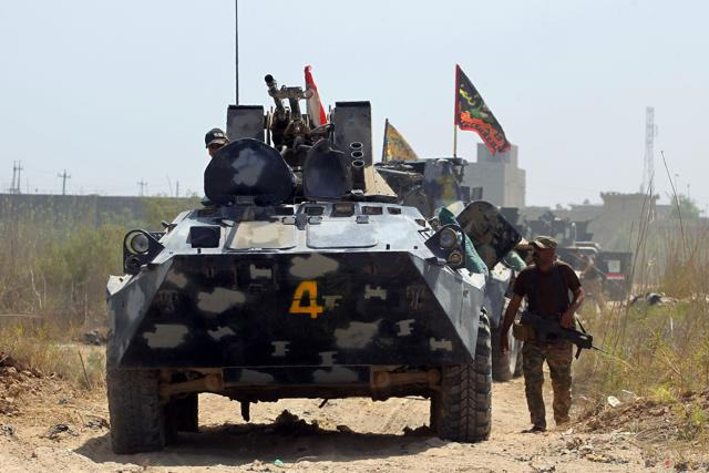 A member of Iraqi government forces walks next to an armoured vehicle during an operation, backed by air support from the US-led coalition, in Fallujah's southern Shuhada neighbourhood to retake the area from the Islamic State (IS) group on June 15, 2016.