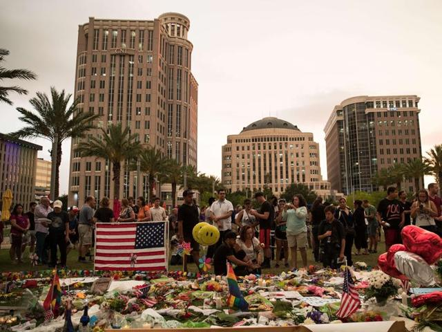 People visit a memorial for the victims of the Pulse Nightclub shooting, at the Dr. Phillips Center for Performing Arts, June 14, 2016 in Orlando, Florida.