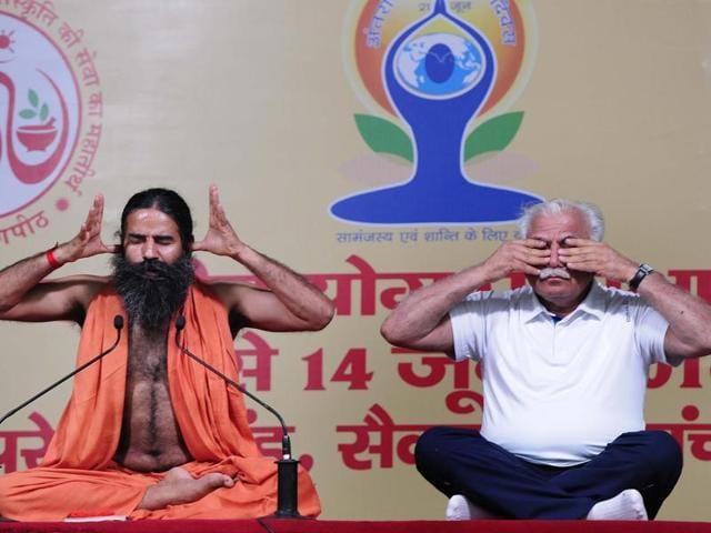 Yoga guru Ramdev and Haryana CM Manohar Lal Khattar during a yoga camp in Panchkula on Tuesday.