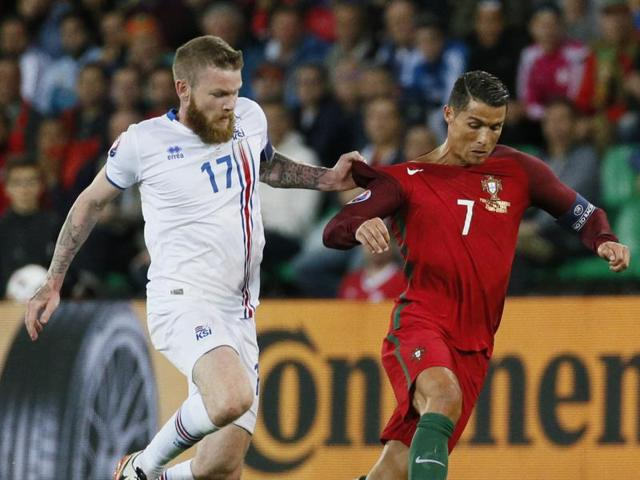 Iceland's midfielder Aron Gunnarsson (L) and Portugal's forward Cristiano Ronaldo vie for the ball during the Euro 2016 group F football match between Portugal and Iceland at the Geoffroy-Guichard stadium in Saint-Etienne on Wednesday.
