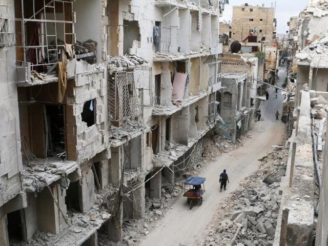 Residents walk near damaged buildings in the rebel held area of Old Aleppo, Syria, May 5, 2016.