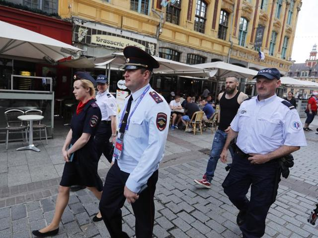 Russian police officers walk through a square in downtown Lille, after being called into to bolster security ahead of the Euro 2016 Group B football match between Russia and Slovakia at the Pierre Mauroy stadium in Villeneuve d'Ascq, near Lille.