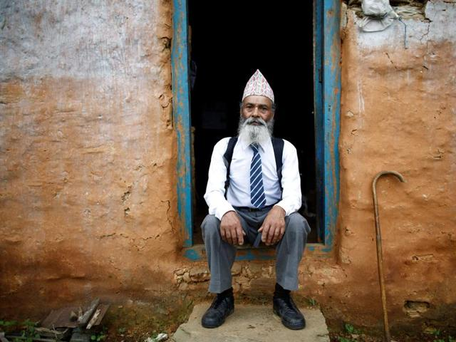Durga Kami poses for a picture wearing his school uniform at the door of his one-room house in Syangja, Nepal.