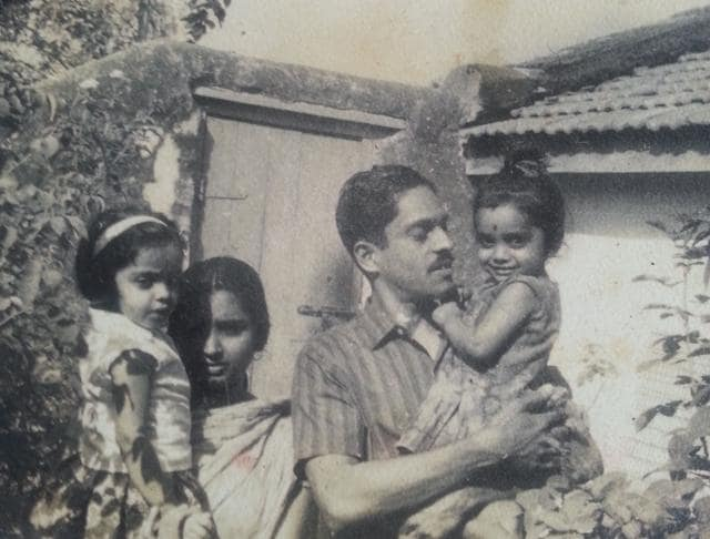 Sudha Menon, aged 3, with her father in a family photo that also shows her mother and sister.