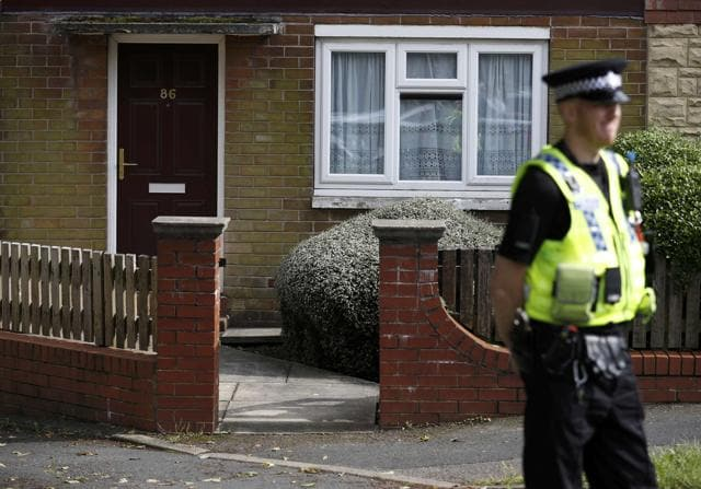 A police officer stands outside the home of a man who was arrested after Labour MP Jo Cox was attacked in her constituency near Leeds.
