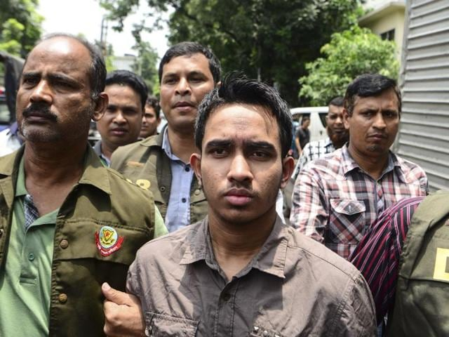 Members of Bangladesh Police's Detective Branch escort Mohammad Sumon Hossain in Dhaka on Thursday. Police counter-terrorism chief Monirul Islam told reporters Hossain was charged with taking part in an attack last October on pubisher Ahmed Rashed Tutul.