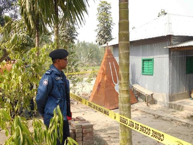 In this file photo, a Bangladeshi policeman stands guard where a top Hindu priest was killed in the remote northern district of Panchagarh.