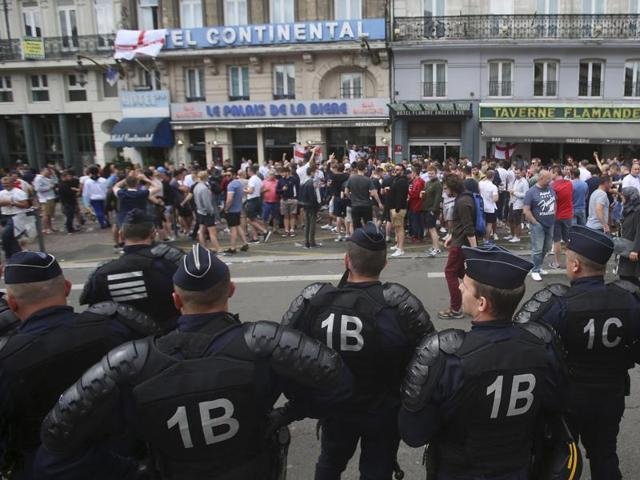 French police watch England fans outside a bar in downtown Lille.