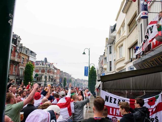 A flare is ignited as England fans hang a flag onto a bar's canopy in central Lens, on the day that England play Wales during the Euro 2016 football tournament.