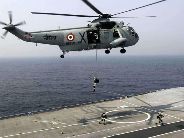 Marine commandoes of the India Navy slither down from a Sea King helicopter during an exercise on board INS Vrat vessel.