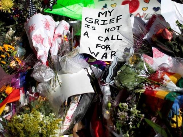 A sign sits atop a pile of flowers at a makeshift memorial to remember the victims of the mass shooting at a gay nightclub in Orlando, outside the Stonewall Inn in Manhattan.