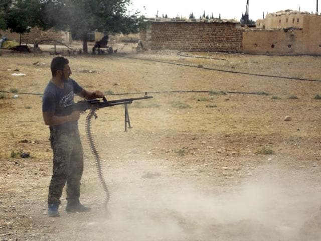 A fighter of Syria's Manbij military council fires a weapon on June 15, 2016 on the outskirts of the northern Syrian town of Manbij, which is held by jihadists of the Islamic State (IS) group.
