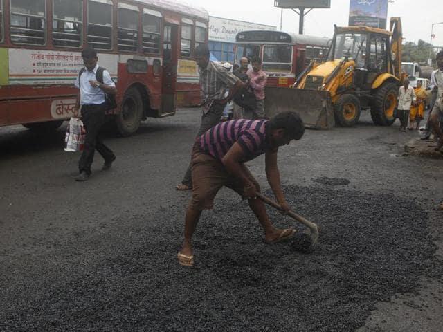 BMC workers filling potholes opposite Mahim church in Mumbai.  (Photo by Satish Bate/ Hindustan Times)