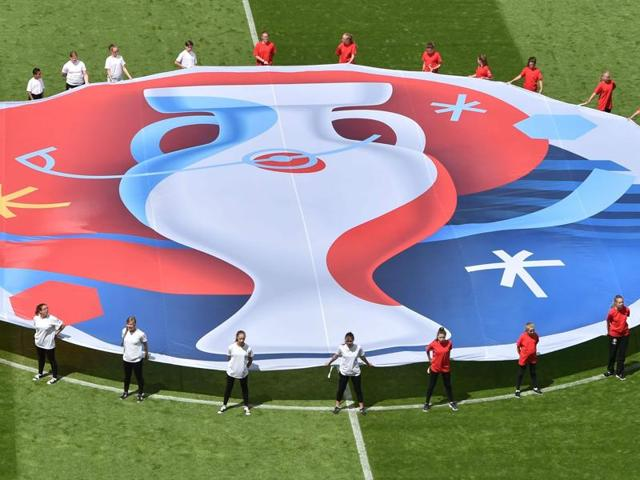 Volunteers perform with a flag showing the logo of the Uefa Euro 2016 football tournament prior to a Group B football match in Lens.