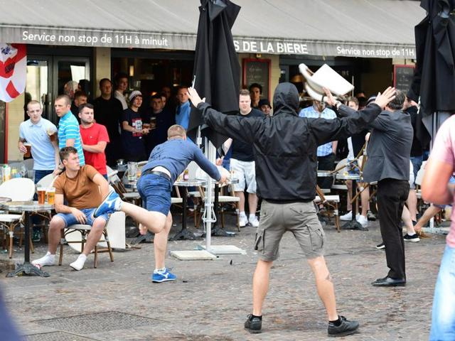 A Russian football supporter lobs a chair towards Slovakian fans sitting in a cafe.