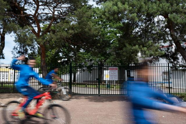 Boys ride bicycles past the entrance of Anatole France secondary school in Venissieux near Lyon, where a 12-year-old boy was stabbed by a 11-year-old.