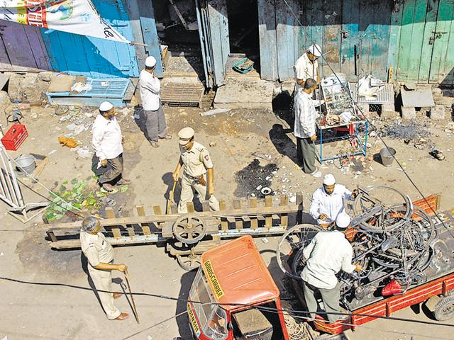 Residents and police officers clear debris at a blast site in Malegaon, about 260 km (162 miles) northeast of Mumbai on September 30, 2008.